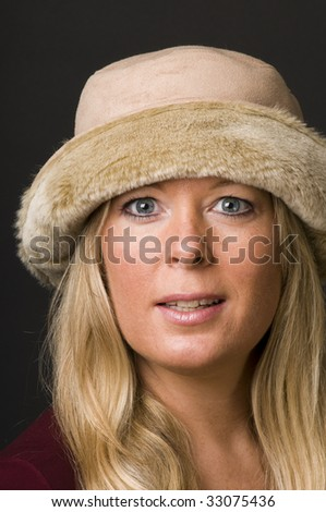 sexy and attractive blond woman in her forties wearing retro vintage fashion hat with expressive face emotion