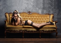 Sexy and beautiful woman in erotic lingerie and stockings posing on a sofa in vintage interior.