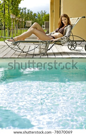 Sexy and beautiful young brunette woman relaxing on deck chair by the pool