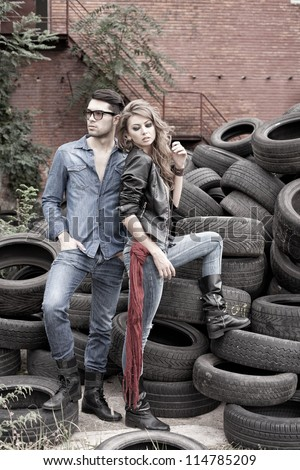Sexy and fashionable couple wearing jeans, shoot in a grungy location - landscape orientation with copy-space