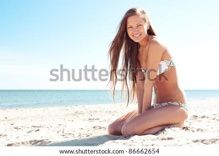 sexy and happy beautiful woman in bikini sitting at the beach