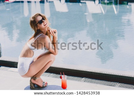 sexy and happy blonde woman in white swimsuit and sandals sitting near cocktail near swimming pool #1428453938