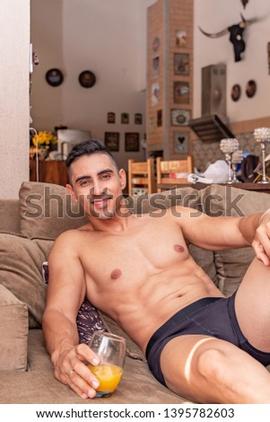 Sexy and muscular young man lying on the couch wearing only a black underwear and drinking a juice.
