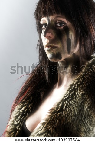 Sexy and mysterious girl partially clothed in fur wearing dark streaks of facepaint