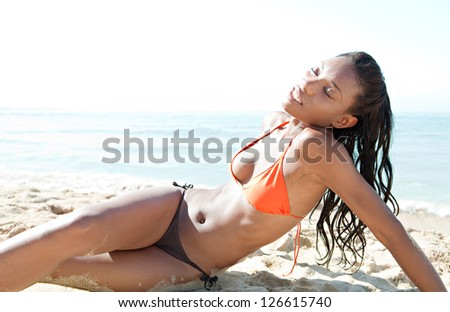 Sexy and sophisticated black woman sunbathing and relaxing on a beach, enjoying the sun while on vacation.