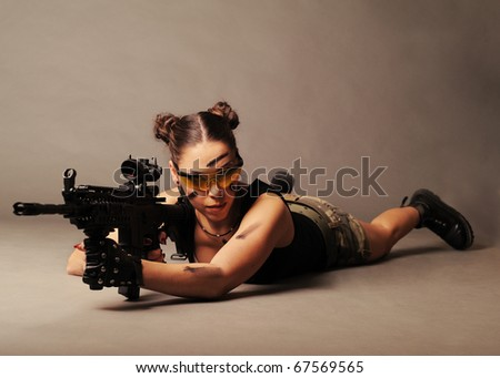 Sexy army woman posing with weapon, on gray background. - stock photo