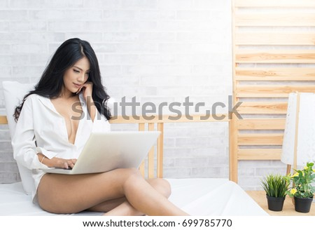 Sexy asian woman with computer notebook on bed