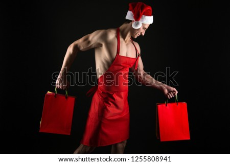 Sexy athletic macho muscular chest in santa claus hat. Athlete muscular man wear santa hat and apron. I have gift for you. Macho muscular torso posing with shopping bags. Santa claus for adult.