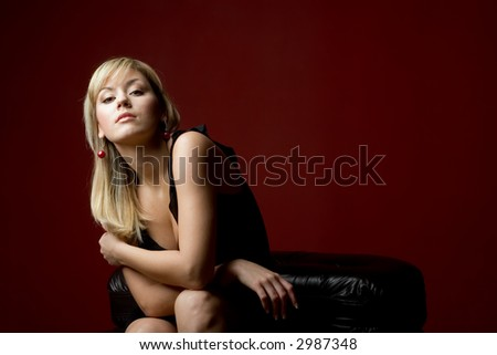 Sexy attractive blond woman in black dress smiling on on black leather sofa on dark red background.