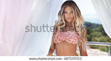 Sexy attractive blonde lady posing in fashionable swimsuit on the beach, sunbathing.