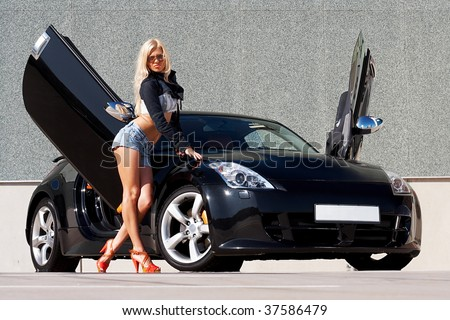 Sexy babe standing in front of tuned supercar - stock photo