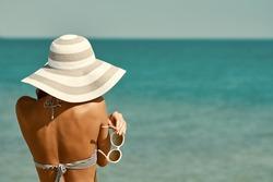 Sexy back of a beautiful woman in bikini, creative hat and sunglasses on sea background. Retro vintage toned image, film simulation.
