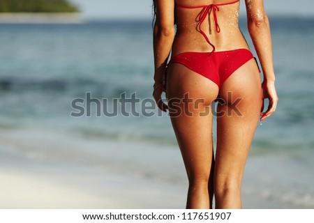 Sexy back of a beautiful woman in red bikini on sea background