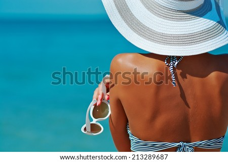 Sexy back of a beautiful woman in striped bikini and hat with creative white sunglasses on sea background.