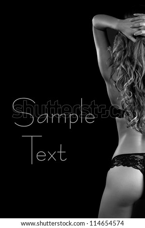 Sexy back of young beautiful blonde in lingerie over dark background. Black&White
