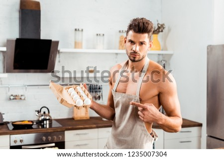 sexy bare-chested man in apron pointing with finger at egg carton