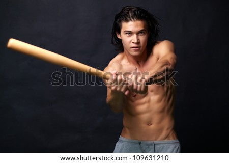 Sexy baseball player aiming a blow with a bat