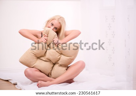 Sexy beautiful blond girl in black underclothes with blue eyes sitting looking out beige pillow and squeezing it  looking camera isolated on white background   with copy place