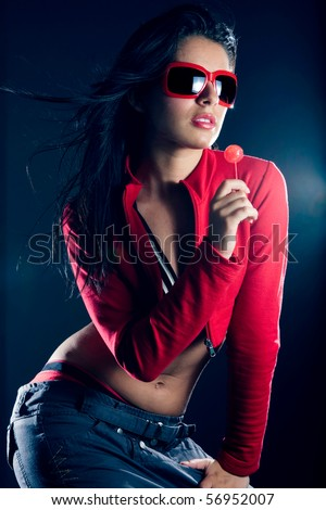 Sexy beautiful dancing hip hop girl with red sunglasses, holding a candy in her hand