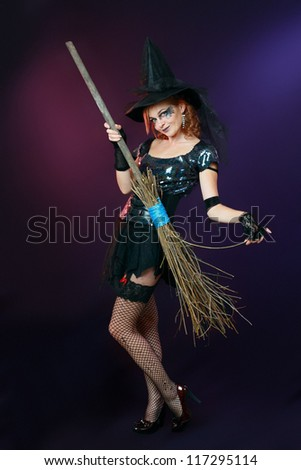 Sexy beautiful witch with broom on dark background