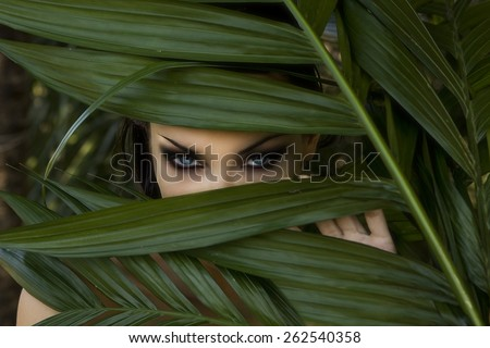 Sexy beautiful woman hiding behind the palm leaves like a panther in the in the tropical forest in India. Portrait of beautiful caucasian stylish young woman with smokey eyes, wildness