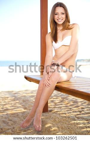 sexy beautiful woman in bikini sitting at the beach