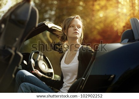 sexy beautiful young woman driving her convertible car