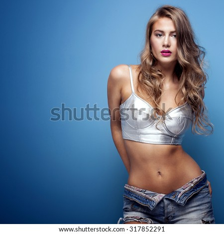 Stock Photo Sexy beautiful young woman posing on blue background, looking at camera. Girl in short jeans and silver fashionable top. Studio shot.