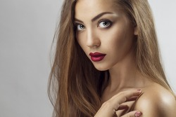 Sexy Beauty Girl with purple-red Lips. Provocative Make up. Luxury Woman with Green Eyes. Fashion Brunette Portrait  on a silver background. Gorgeous Woman Face. Long Hair