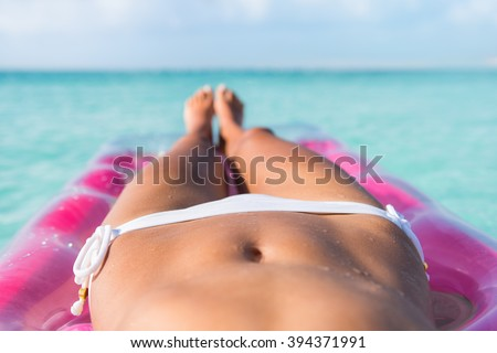 Sexy bikini body abs stomach closeup and tanned legs of beach woman relaxing tanning on air mattress bed on turquoise ocean or swimming pool at a tropical caribbean destination.