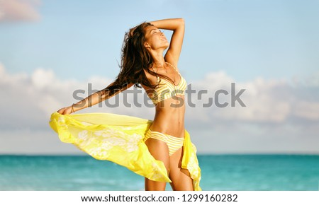 Sexy bikini body woman feeling free with slim stomach and smooth thighs wearing yellow fashion scarf skirt swimwear beachwear showing off weight loss. Laser beauty spa wellness concept.