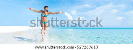 Sexy bikini body woman playful on paradise tropical beach having fun playing splashing water in freedom with open arms. Beautiful fit body girl on travel vacation. Banner crop for copy space. #529269610