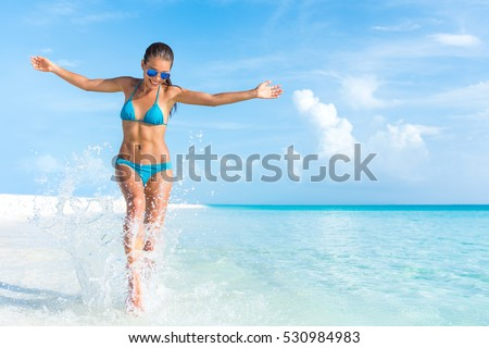 Sexy bikini body woman playful on paradise tropical beach having fun playing splashing water in freedom with open arms. Beautiful fit body girl on luxury travel vacation. #530984983