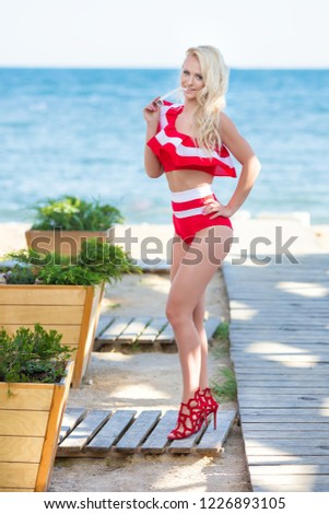 Sexy bikini body woman sun tanning relaxing on perfect tropical beach and turquoise ocean water. Sensual Seducing lady model walking in fashion red swimwear with smooth tanned skin and long lean legs #1226893105