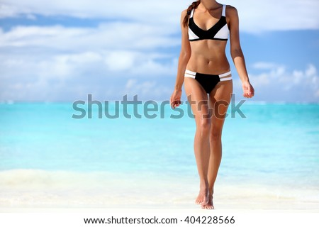 Sexy bikini body woman sun tanning relaxing on perfect tropical beach and turquoise ocean water. Unrecognizable model walking in fashion swimwear with smooth tanned skin and long lean legs. #404228566