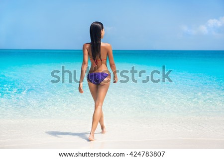 Sexy bikini body woman swimming in turquoise ocean on paradise beach in tropical destination summer Caribbean travel. Model in purple swimwear and suntan skin relaxing sunbathing on holiday.