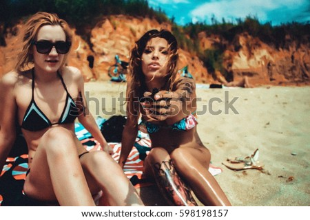 Sexy bikini girls sunbathing and smoking weed on the beach
