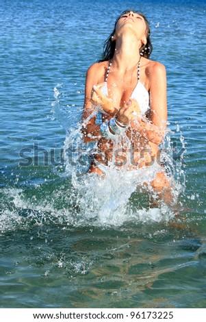 Sexy bikini model having fun in the ocean on vacation