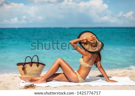 Sexy bikini woman tanning relaxing on beach. Suntan concept. Unrecognizable female adult from the back lying down with straw hat sunbathing under the tropical sun on Caribbean vacation. #1425776717