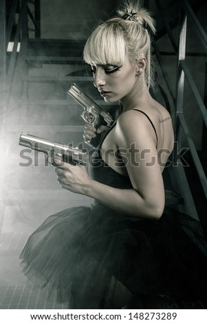 Stock Photo Sexy blonde ballerina dress and pistols