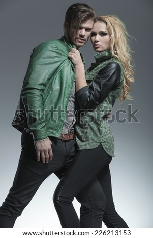 Sexy blonde fashion woman pulling her boyfriend by the collar, both looking at the camera.