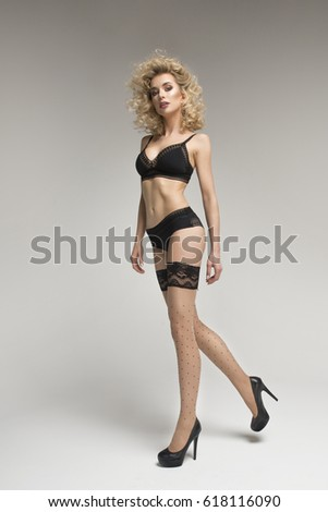 Sexy blonde girl in black lingerie and Stockings over light background #618116090