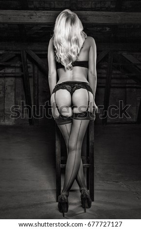 Sexy blonde model posing at stool in underwear in darkness black and white