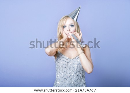 Sexy blonde party girl wearing silver dress and blowing party whistle