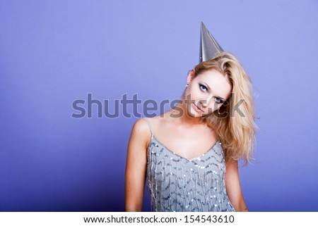 Sexy blonde party girl wearing silver dress and party hat