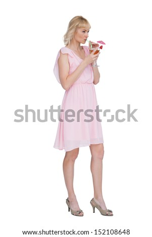 Sexy blonde posing while drinking cocktail and looking away against white background