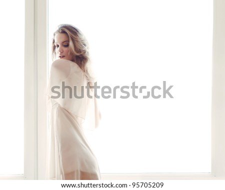 sexy blonde standing near the window