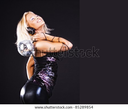 Sexy blonde with disco ball enjoys music at party