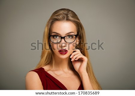 Sexy Blonde Woman in Red Fashion Dress and Glasses on Gray Backgound
