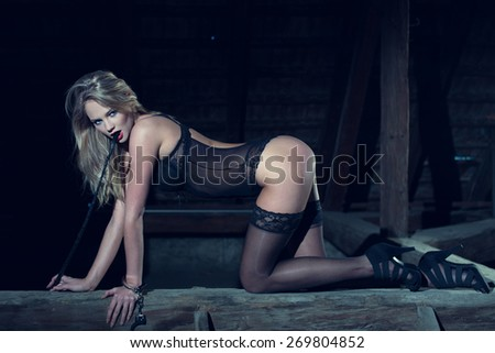 Sexy blonde woman in underwear kneeling on timber with whip, bdsm